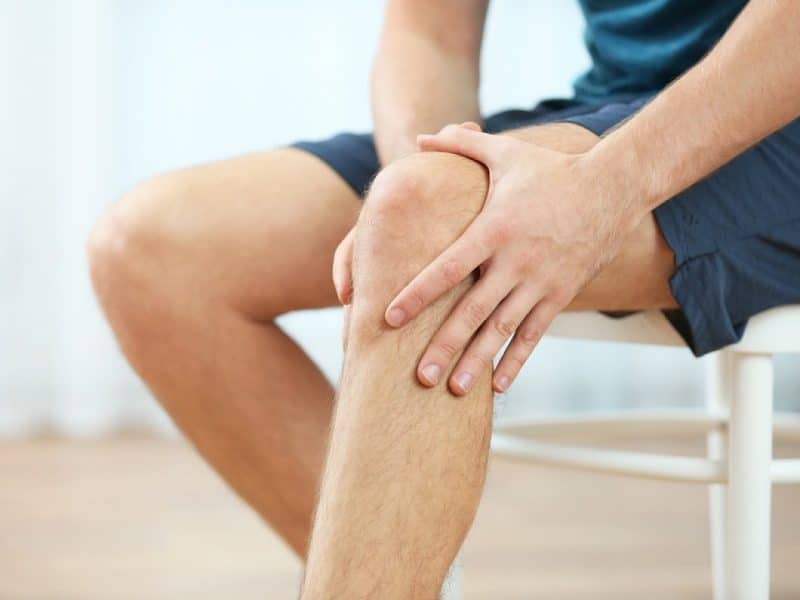 Clos image of man holding his sore knee